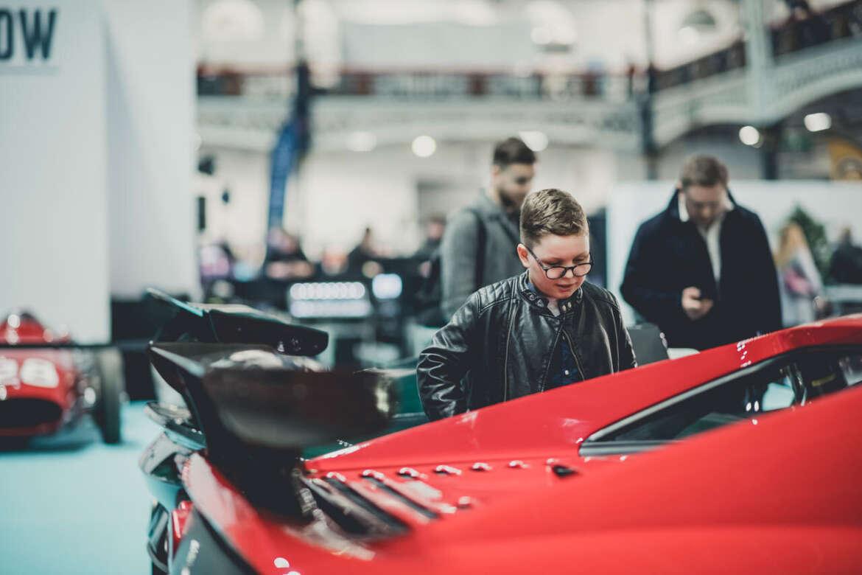 Boy admiring a Ferrari at a car show